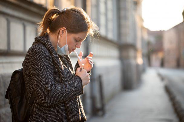 Jeune femme allumant une cigarette avec son masque sous le menton