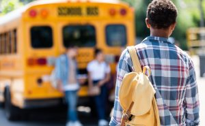Adolescent de dos devant un autobus